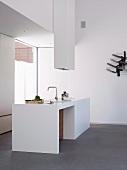 White, designer minimalist kitchen island with extractor hood in corner of room with floor-to-ceiling window