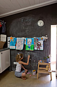 Girl drawing on blackboard wall in utility room