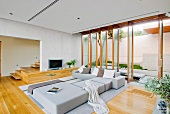 Minimalist sofa combination in front of open floor-to-ceiling windows in modern living room with parquet floor
