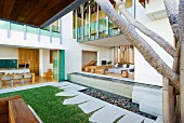 View into kitchen and living room of modern house with open, panoramic facades leading to manicured garden