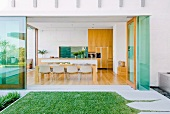 Glass-fronted dining room in modern, architect-designed house with access to manicured garden