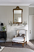 Elegant living room with armchair in front of disused fireplace, candelabras on mantelpiece and antique mirror