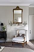 Elegantes Wohnzimmer mit Sessel vor stillgelegtem Kamin, Kerzenleuchter auf dem Sims und Antikspiegel