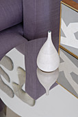 White ceramic vase on reflective side table in front of partial view of sofa