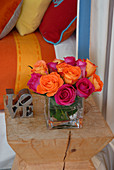 Pink und orangefarbener Rosenstrauss auf Designer-Hocker; Kissen und Bettdecke in korrespondierenden Farben im Hintergrund