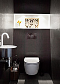 Tiled designer bathroom with chrome wash basin and picture with butterfly motif on broad light strip