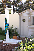Garden with DIY outside shower in front of a small garden house