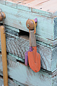 Gardening tools hanging from potting table made from wooden pallets