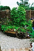 Garden ornaments in front of raised bed of flowers
