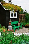 Garden shed with turf roof and green-painted bench