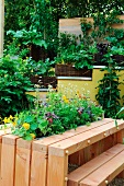 Table with integrated planter in front of potted herbs on stepped garden wall
