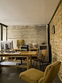 Rustic office with exposed concrete wall and stone wall - vintage-style seating around simple desk