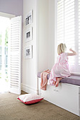 Girl sitting on window seat built into niche of window with closed, white, slatted shutters