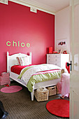 Child's bedroom with white, traditional bed against red wall with stucco frieze