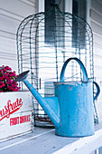 Vintage watering can in front of a bird cage on a wooden table