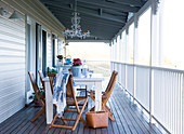 Simple table and chairs on the veranda of a wooden country home