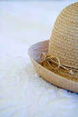 Partially visible ladies straw hat on a white quilt