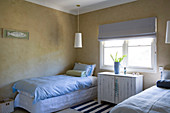 Simple bedroom with a single bed, a hanging lamp above it and chest of drawers under the window