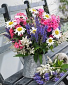 Summer bouquet in a zinc pitcher on a garden bench