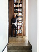 View of tall bookcase with vintage ladder from stairwell