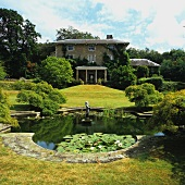 Summer atmosphere in park-style garden with pond in front of grand country house