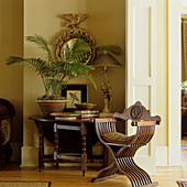 Detail of modern interior - antique wooden chair next to folding console table