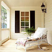 White wicker couch on veranda of traditional country house