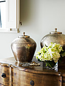 Traditional metal vessels on antique wooden chest of drawers against wall