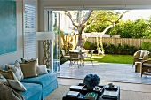 View from living room with turquoise elements to garden terrace adjoining green lawn