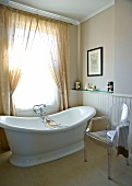 Designer chair and free-standing vintage bathtub below window with curtain in simple bathroom
