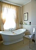 Designer chair and free-standing vintage bathtub below window with curtain in simple bathroom