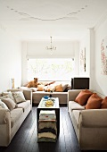 Bright living room with three sand-coloured sofas and colour-coordinated scatter cushions
