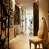 Unusual chair with brocade-patterned upholstery in elegant hallway of house with gallery of pictures and stone-flagged floor