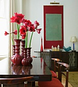 Shades of red in dining room with retro furniture - amaryllis in decorative ceramic vases and modern artwork in background