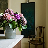 Bouquet of hydrangeas on kitchen counter; dark blue painting and antique wooden chair in background