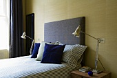 Bedroom with vintage lamps either side of bed with upholstered headboard and blue scatter cushions against sand-coloured fabric wallpaper