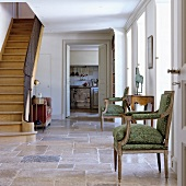 Antique chair with upholstered seat and old wooden staircase in stone-flagged foyer of Mediterranean country house