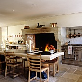 Vintage kitchen with dining table in front of open fireplace in Mediterranean country house