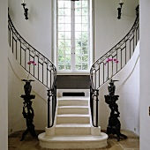 Foyer of Mediterranean country house with central steps leading to two staircases