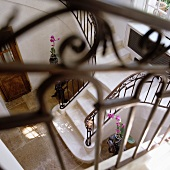 View down onto marble staircase with wrought iron balustrade in foyer of Mediterranean villa