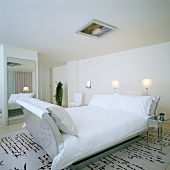 Room in elegant London hotel; rug with pattern of hand-writing, designer sleigh bed and framed picture on ceiling