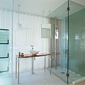 Glass ensuite hotel bathroom with floor-level shower and modern washstand with Philippe Starck tap fittings in front of translucent curtain leading to bedroom