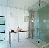 Gläsernes Bad Ensuite im Hotel - mit bodengleicher Dusche und modernem Waschtisch mit Philippe Starck Armatur vor transluzentem Vorhang zum Schlafzimmer