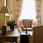 Table lamp on table next to lounge area - elegant armchairs and coffee table in front of window with gathered curtains