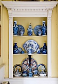 Collection of valuable, Chinese porcelain in fitted shelving with classicist-style wooden frame