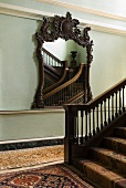 Mirror with ornately carved wooden frame, stucco elements on walls and Oriental-patterned rugs and runners in traditional stairwell