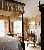 Bedroom with antique English furniture and floral wallpaper