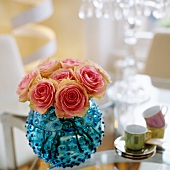 Pink roses in spherical, blue glass vase and mocha cups on table