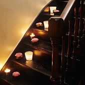 Lit candle lanterns and roses on old, dark wood staircase treads