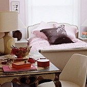 Red wooden boxes on vintage table with traditional sleigh bed in background